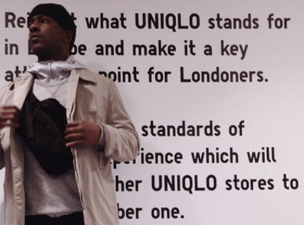 Skepta standing in front of Uniqlo motto