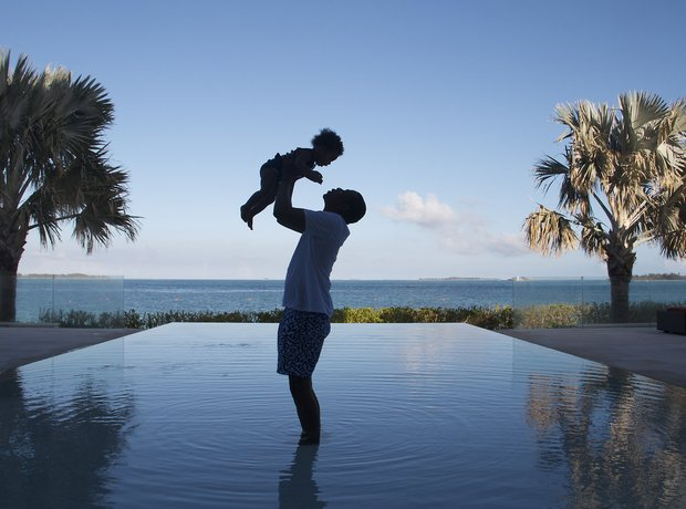 Jay Z holding up Blue Ivy Carter next to swimming pool.
