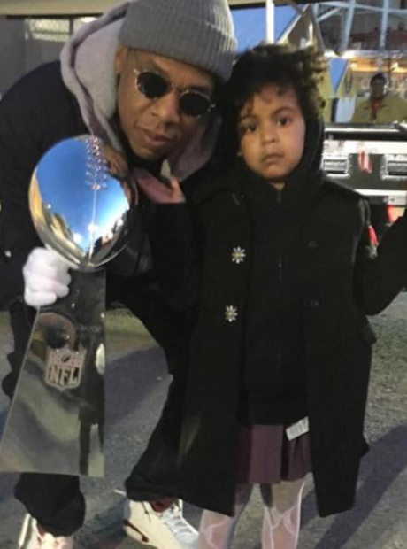 Jay Z holding Superbowl trophy with Blue Ivy
