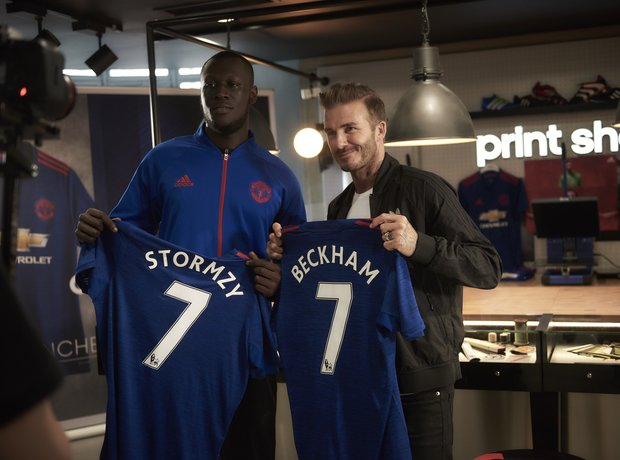 Stormzy and David Beckham holding football shirts