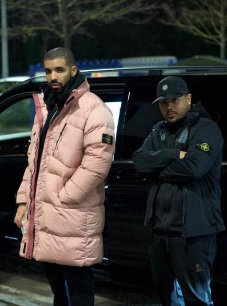Drake in a pink Stone Island coat