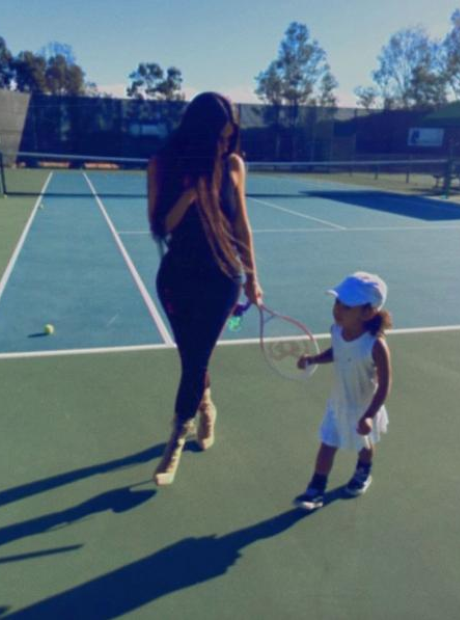 Kim Kardashian and North West playing tennis.